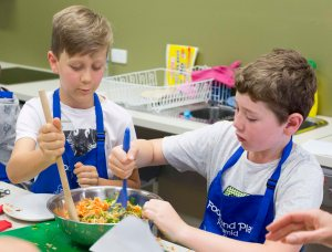 Boys mixing grated veg for muffins